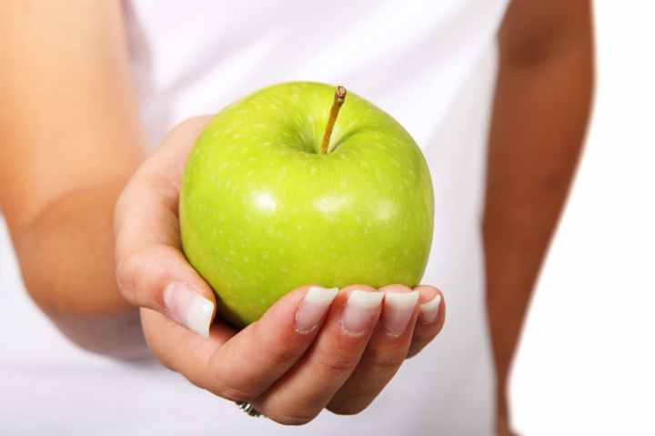green apple in woman hand
